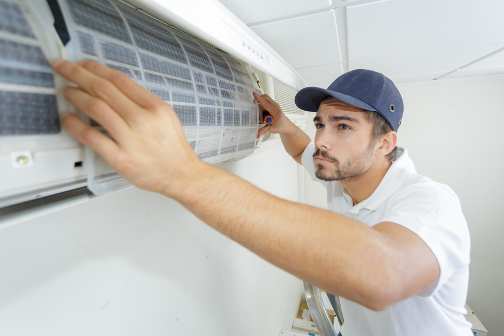 Technicien HVAC qui entretien l'air conditionné