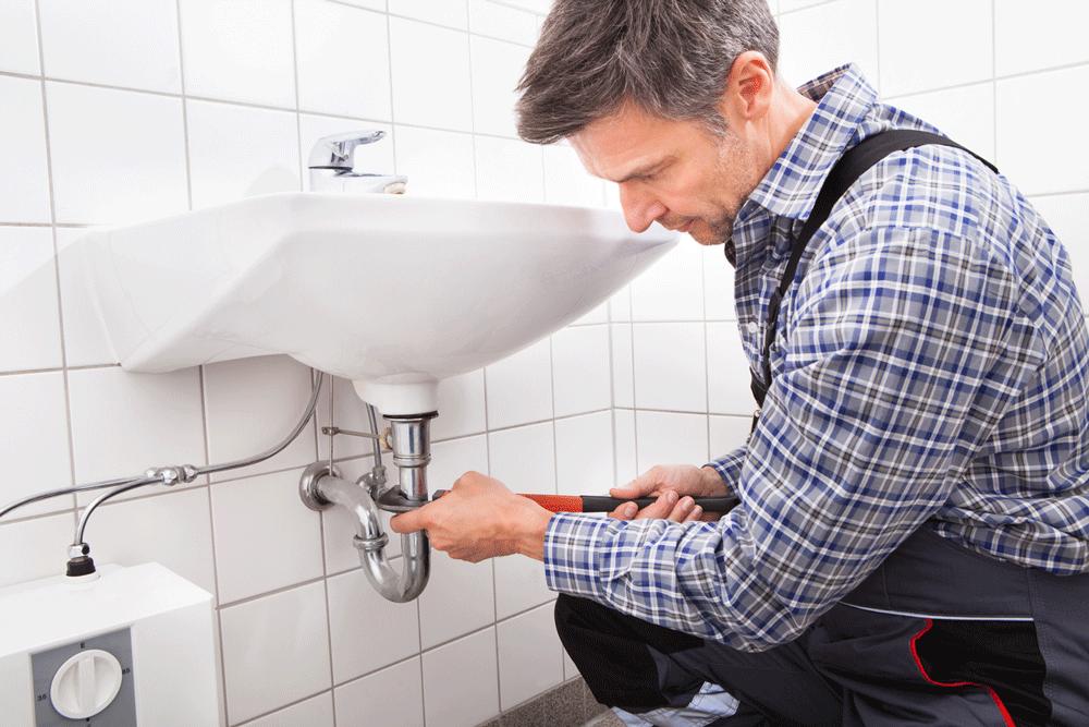Plombier réparant un évier bouché